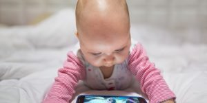 bebelus se uita pe telefon