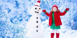 fetita cu om de zapada iarna