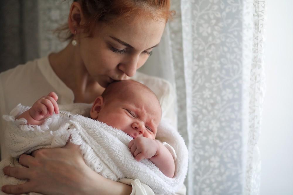 bebe rasfatat in brate la mama