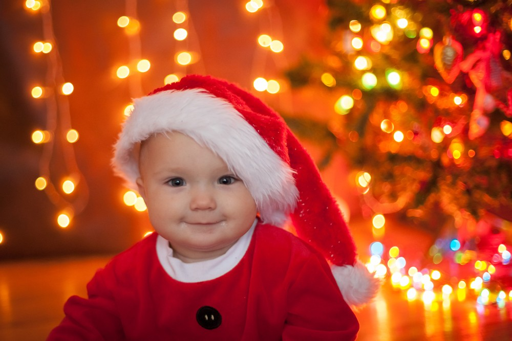 bebe in costumas rosu si caciulita de Craciun